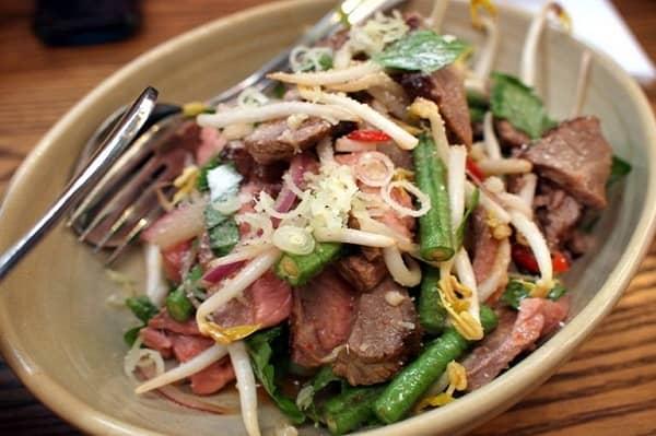 Thịt bò tái được cắt lát mỏng sau đó ướp với nước cốt chanh và trộn thêm các gia vị