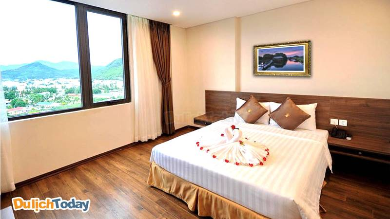 Phòng ngủ tại Lenid với ga giường trắng tinh và cửa sổ hướng biển cực lãng mạn