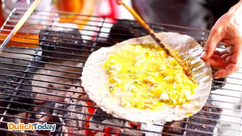 Cho trứng trên bề mặt bánh và nướng bánh trên than hồng