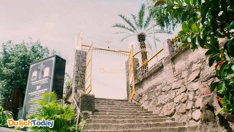 Bậc thang đá đưa du khách vào khuôn viên nhà thờ, bên cạnh là mộ phần linh mục Louis Vallet