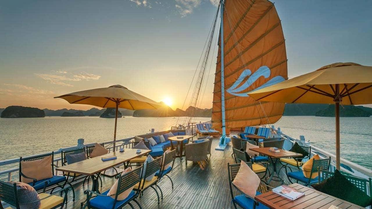 Nhâm nhi đồ uống và ngắm cảnh hoàng hôn trên vịnh Hạ Long từ boong tàu. Nguồn: Internet