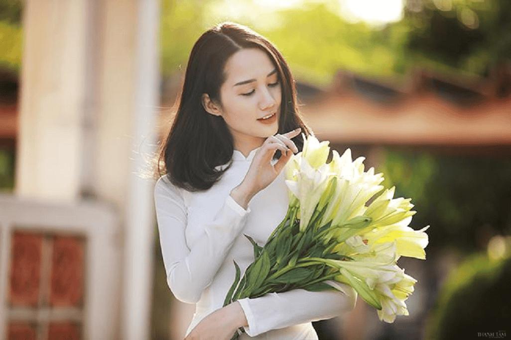 Nét đẹp thanh khiết của em bên tà báo dài cùng đóa hoa loa kèn trắng muốt