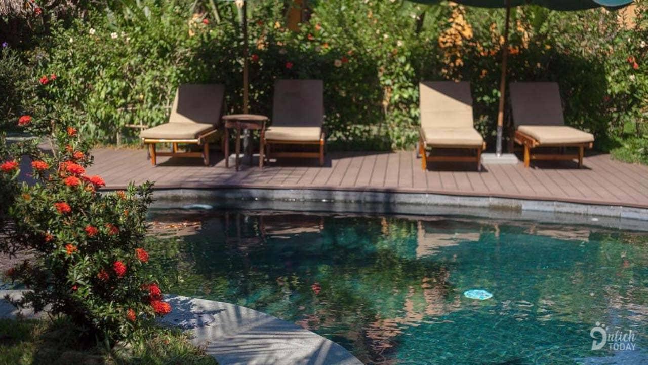 Hồ bơi xanh mát cùng với những chiếc ghế dài để du khách có thể tắm nắng và thư giãn