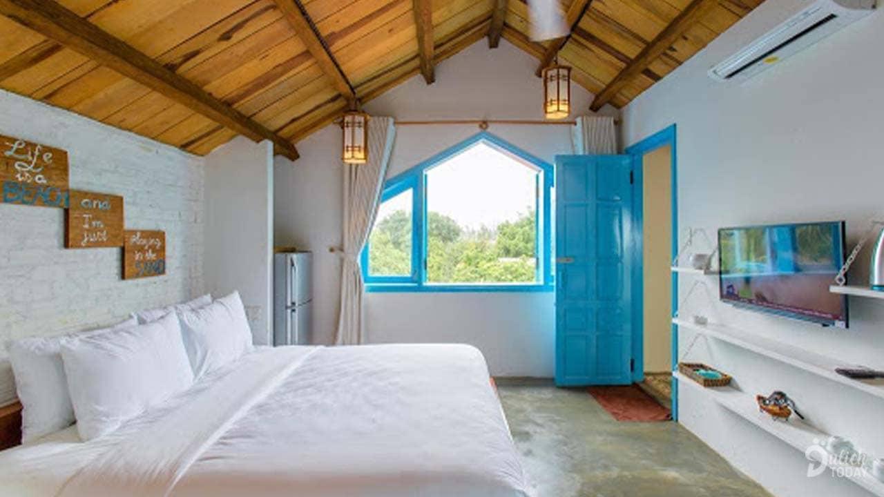 Phòng tiêu chuẩn giường đôi với tone màu xanh-trắng có kích thước 30m2 đẹp và có view nhìn ra vườn