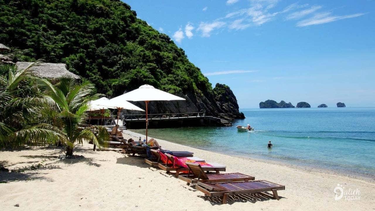 Du khách nằm thư giãn trên bãi biển ngắm vịnh Lan Hạ ngay trong tầm mắt